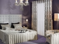 Moderná spálňa s klasockými látkami sivej farby.